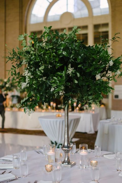 a lush greenery centerpiece on a tall stand is an elegant decor option