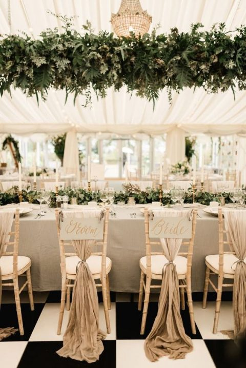 a lush greenery decoration over the reception table and a matching garland on it