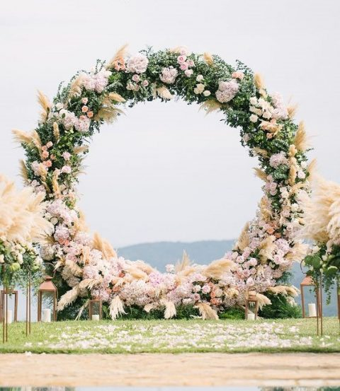a lush greenery, pampas grass and pink blooms circular wedding arch