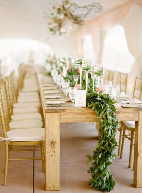 a lush greenery table runner and tall candle holders with grass