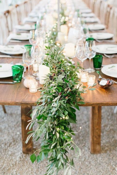 a lush greenery table runner with berries is a cool idea for a summer wedding
