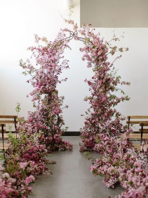 a lush prink floral wedding arch with aisle lining looks very spring-like and very romantic