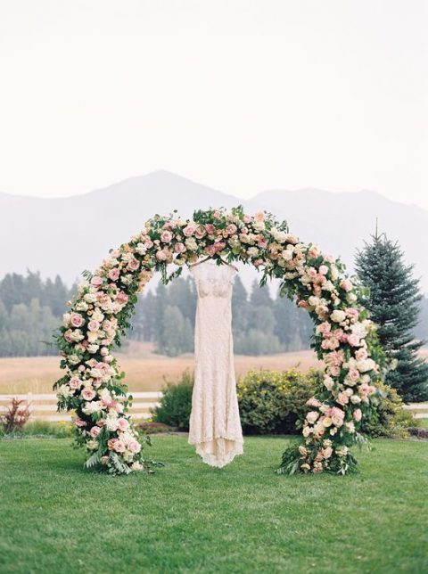 a lush semi circular wedding arch with greenery and blush blooms and a blush wedding dress