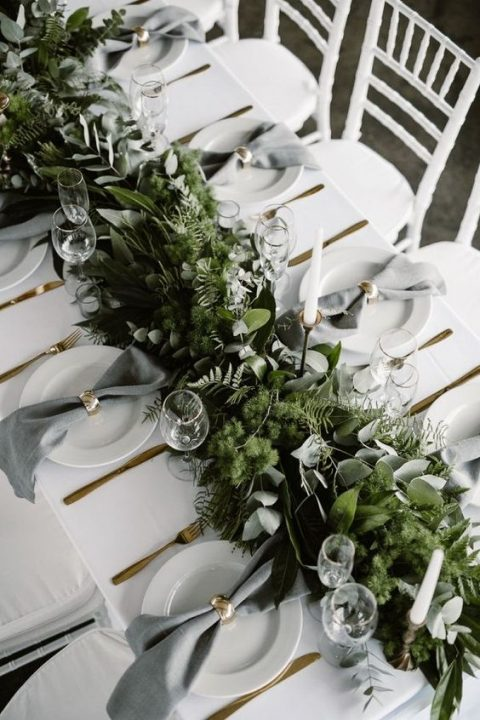 a lush woodland-inspired greenery table runner with various kinds of eucalyptus, moss and ferns