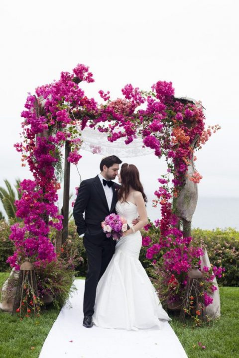 a luxurious and bright fuchsia bloom wedding arch and a backdrop of the sea behind is a perfect combo