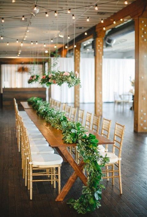 a luxurious greenery table runner with lots of succulents and air plants plus hanging centerpieces over the table
