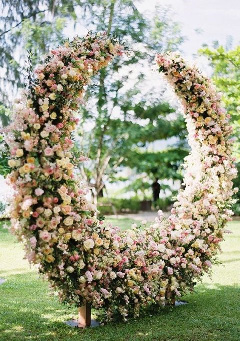 a luxurious lunar-inspired floral wedding arch of pink and blush roses and greenery