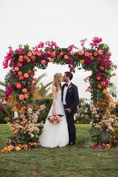 a luxurious tropical wedding arch with tropical leaves, orange, yellow, pnk and fuchsia blooms