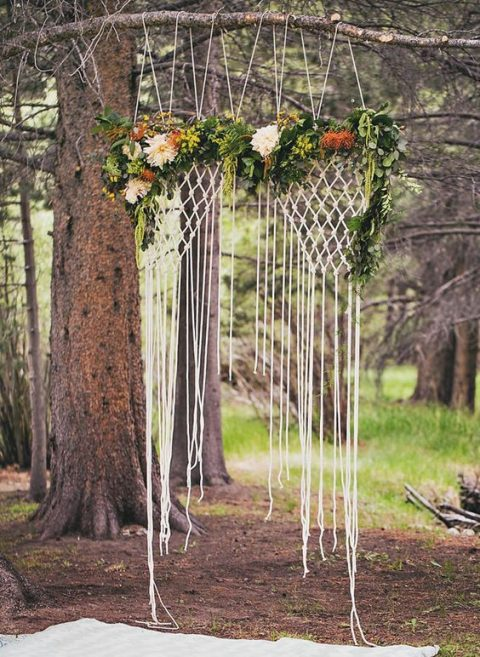 a macrame hanging backdrop with flowers is ideal for a woodland boho wedding