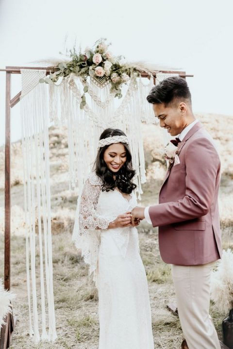 a macrame wedding backdrop was done with lush florals and pampas grass plus long fringe