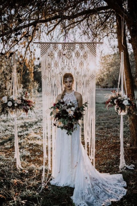 a macrame wedding backdrop with potted haging florals on both sides