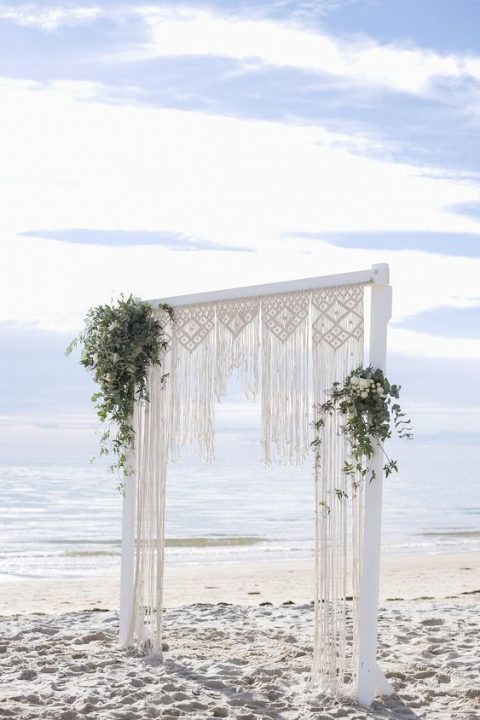 a marcrame wedding arch with greenery and white blooms for a beach boho wedding