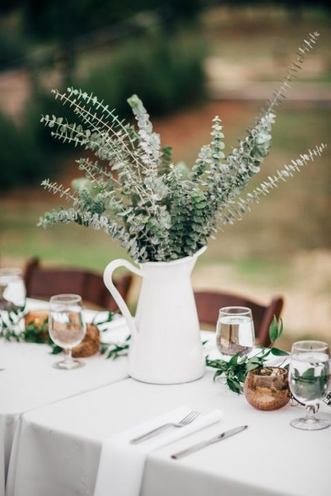 a milk jug with fresh eucalyptus is a simple and rustic wedding centerpiece idea