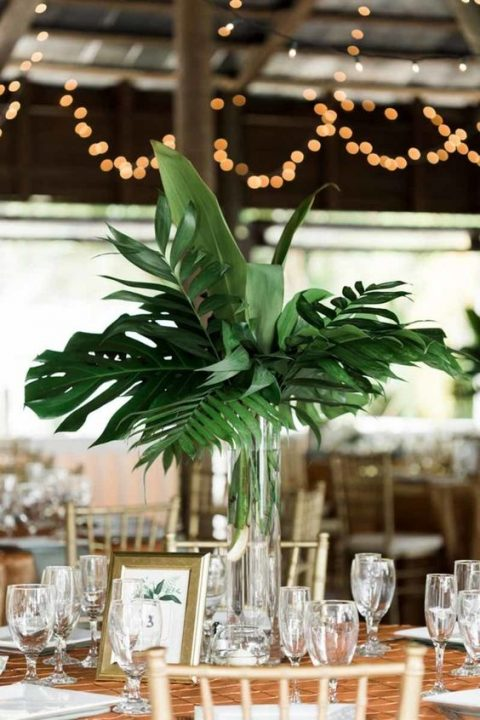 a modern tropical leaves wedding centerpiece in a clear glass vase