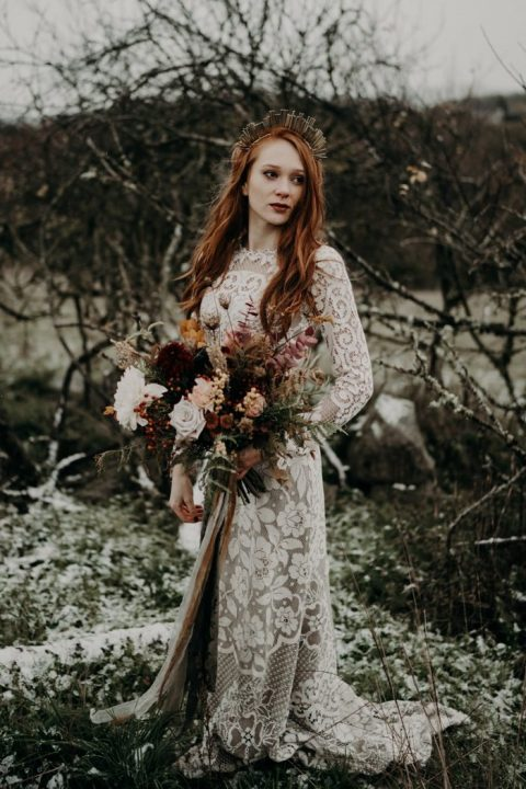 a moody fall bride wearing a unique metallic crown and long red hair down