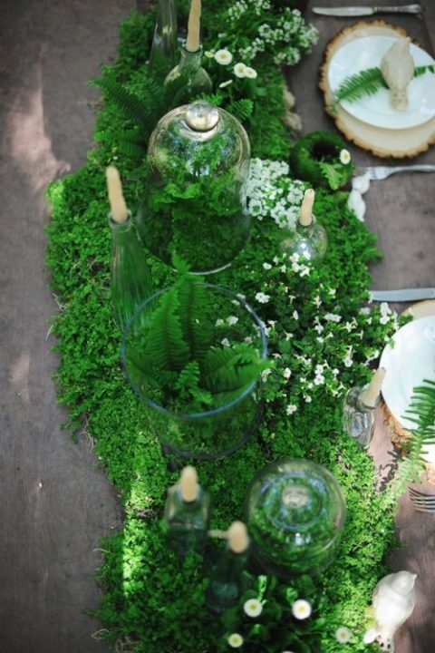 a moss and fern table runner with tiny white blooms and candles