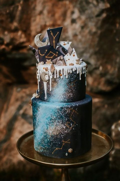 a navy and light blue celestial wedding cake with white dripping, chocolate shards and tiny meringues