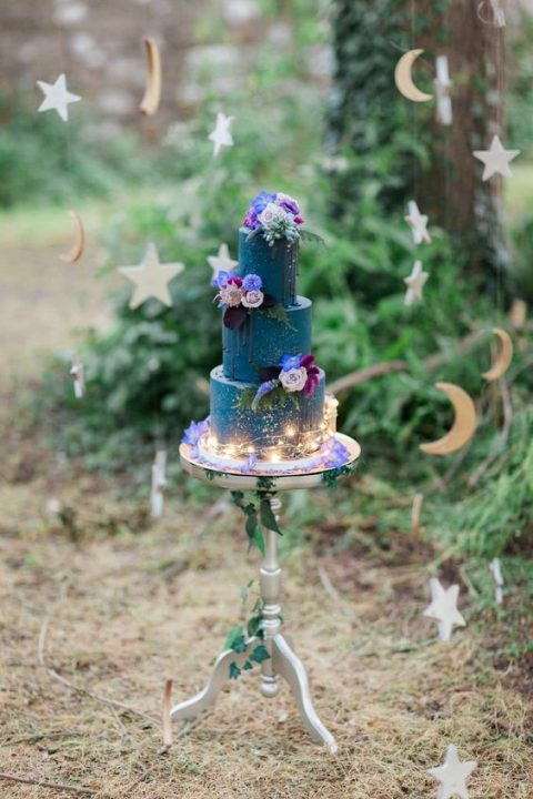a navy celestial wedding cake with bright florals and lights