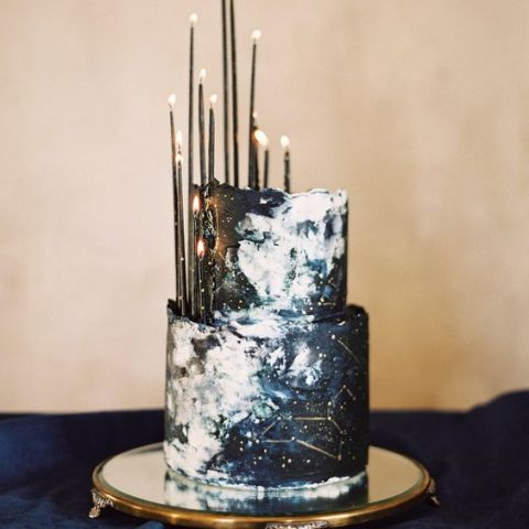 a navy celestial wedding cake with thin black candles on top