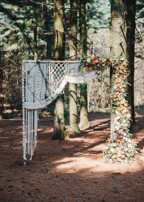 a partly macrame arch and partly a living tree covered with peachy and red blooms