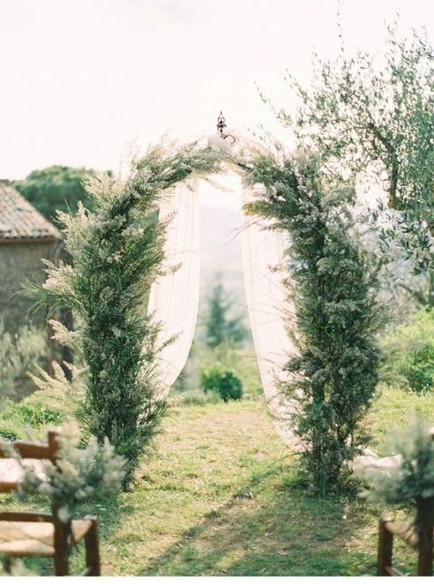 a rustic greenery arbor perfectly fits the casual elegance of the Tuscan countryside