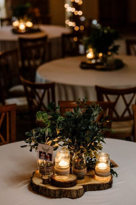 a simple greenery wedding centerpiece with textural foliage, a candle in a jar, a photo and wood slices