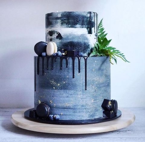 a slate grey wedding cake with navy drip, gold touches, greenery and navy and cream macarons