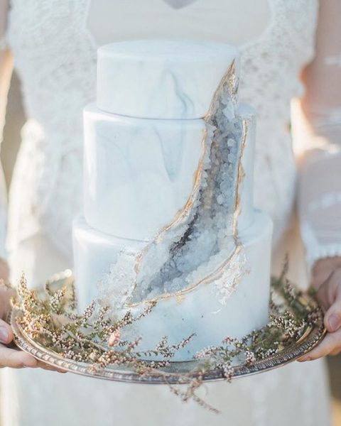 a subtle grey marbleized wedding cake with geodes and gold leaf