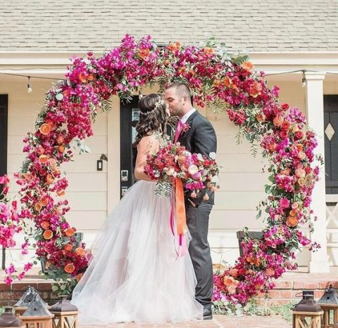 a super bold circular wedding arch with fuchsia, pink, orange blooms and citrus