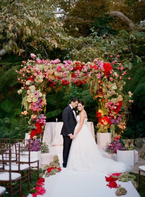 a super colorful wedding arch in red, purple, pink and green plus cascading greenery