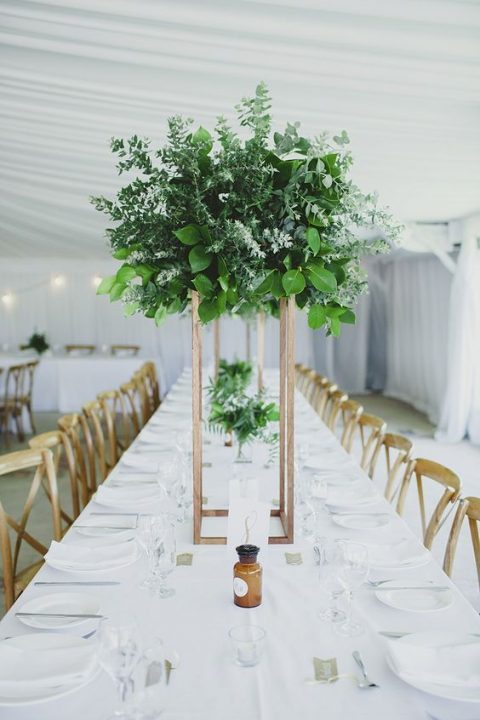 a tall greenery centerpiece of various types of eucalyptus and some foliage on a copper stand