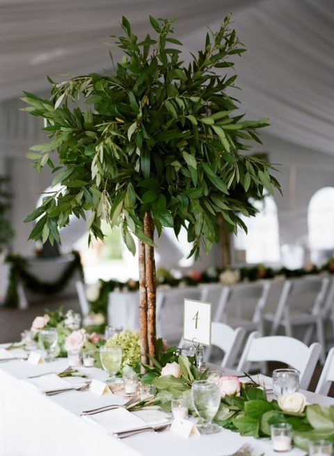 a tall greenery centerpiece on branches brings a natural feel to the table