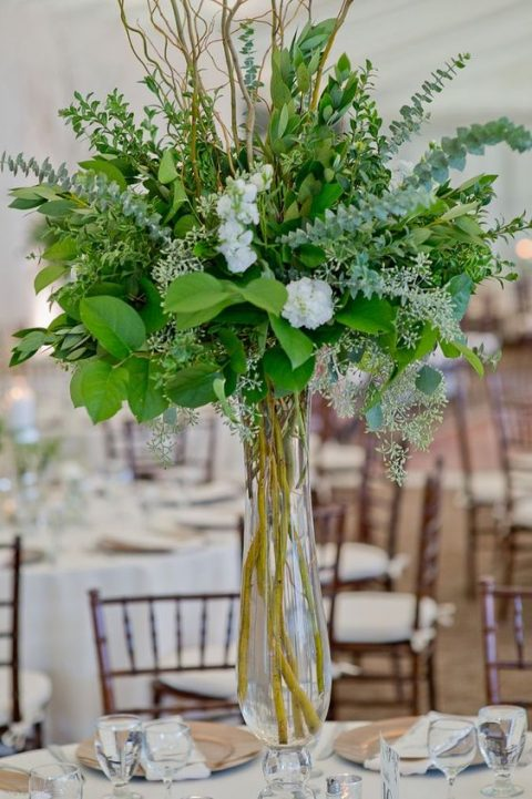 a tall greenery centerpiece with a clear vase, lots of foliage and pale greenery plus a couple of white blooms