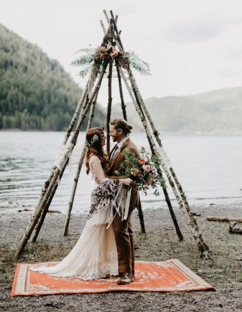 a teepee-shaped altar of birch branches and flowers on top on a lake shore