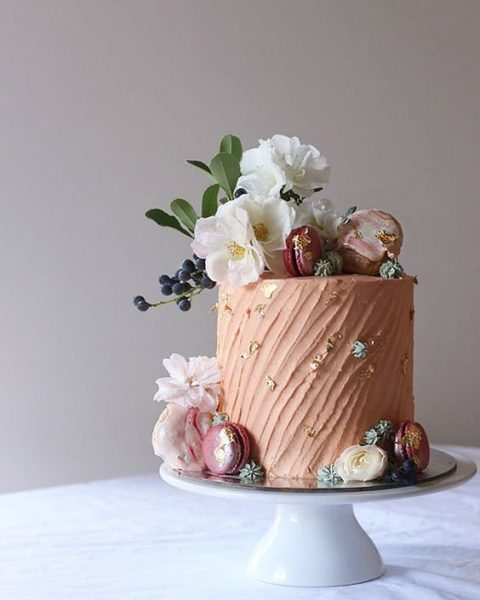 a tender textural blush wedding cake with gold leaf topped with fresh blooms