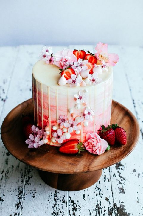 a tender watercolor pink and coral wedding cake with cream drip, cherry blossom and cut strawberries on top and sides