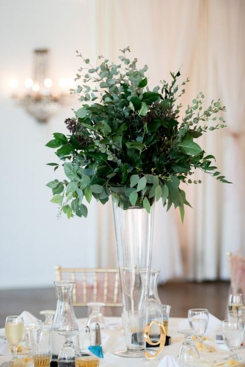 a textural lush greenery centerpiece with much foliage plus a gold table number