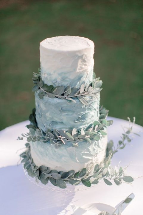 a textural ombre buttercream wedding cake topped with eucalyptus