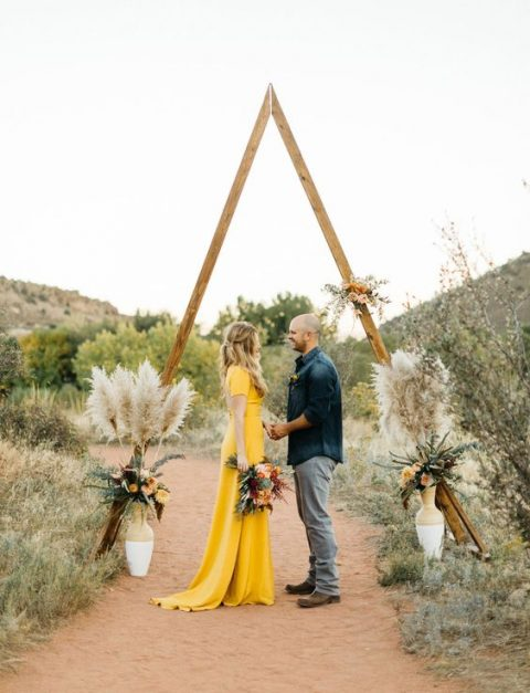 a triangle altar styled with flowers and pampas grass for a boho wedding