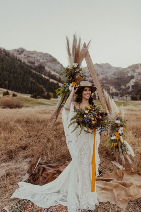 a triangle wedding arch decorated with bright blooms and pampas grass is a cool boho idea