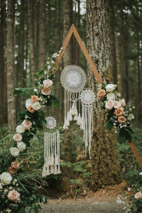 a triangle wedding arch decorated with taupe and white roses plus dream catcher decorations