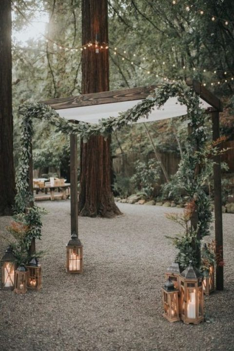 a wedding chuppah decorated with a lush greenery garland and candle lanterns