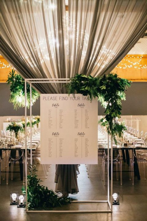 a wedding seating chart done with a frame, a chart and lush greenery in the corners