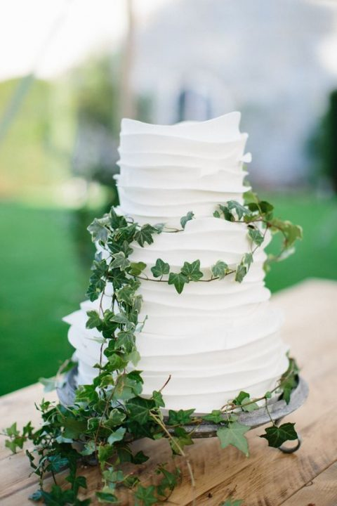 a white ruffle wedding cake decorated only with fresh greenery is a cool idea