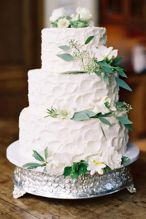 a white textural wedding cake topped with white blooms and greenery for an elegant rustic wedding