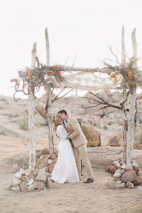 a whitewashed wooden chuppah with a macrame hanging above, feathers and flowers