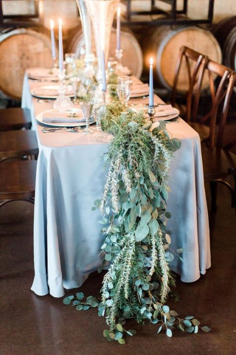 a wild-looking greenery table runner going to the floor and grey canldes plus a grey tablecloth