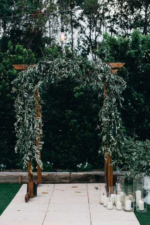 a wooden wedding arch decorated with olive branches, pillar candles around