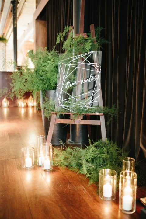 acrylic wedding signage with much fern around and pillar candles for a modern wedding