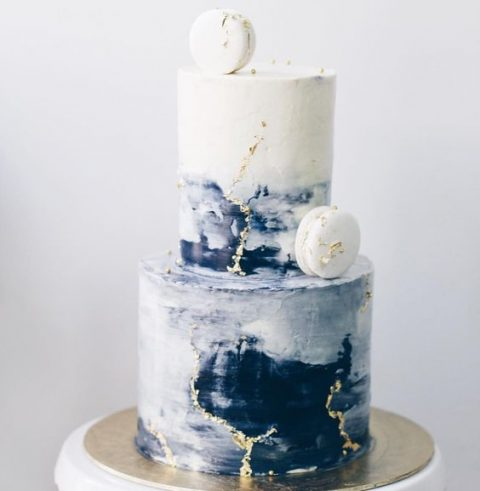 an ombre blue buttercream wedding cake with gold leaf touches and white macarons